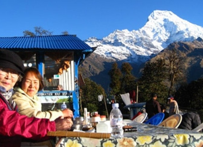 Annapurna south (7219m) and trekkers are taking pleaser - Taken from Ghandruk village.