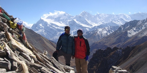 The man posing for a photo and Annapurna range