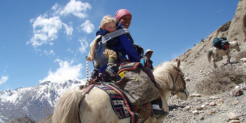The people are riding horses in Mustang