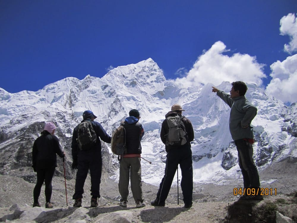 This picture is taken from way to Everest base camp. The soaring mountain is the Nuptse(7864m)  at in front of the trekkers. The trail is became slightly herder because of thin air. The trail also rocky and sandy all the way to Mount Everest base camp.